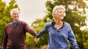 Older couple walking hand in hand outdoors