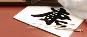 Acupuncture needles resting on Chinese Calligraphy